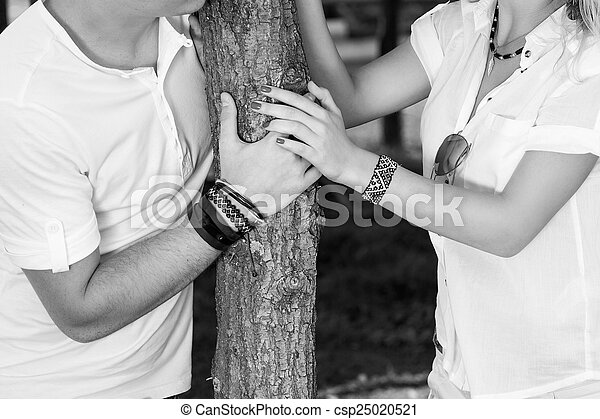 Couple dressed in white, holding hands black and white - csp25020521
