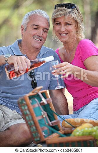 Couple enjoying a picnic together - csp8485861
