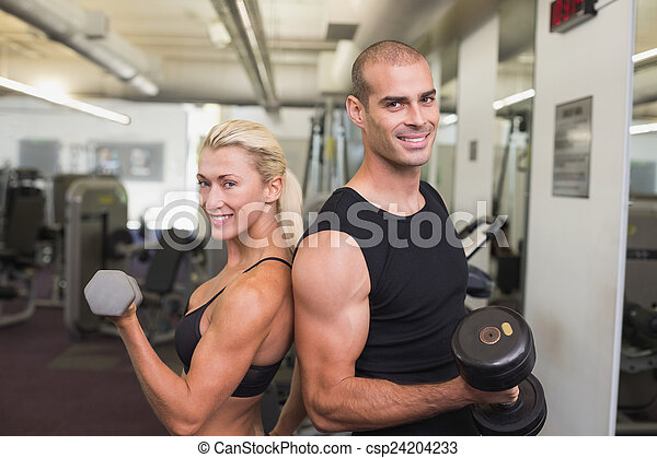 Couple exercising with dumbbells in gym - csp24204233