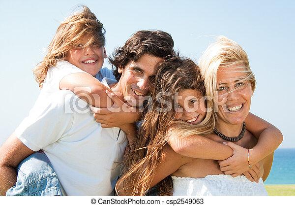 Couple giving children piggyback rides smiling