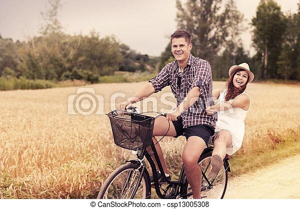 Couple have fun riding on bike - csp13005308