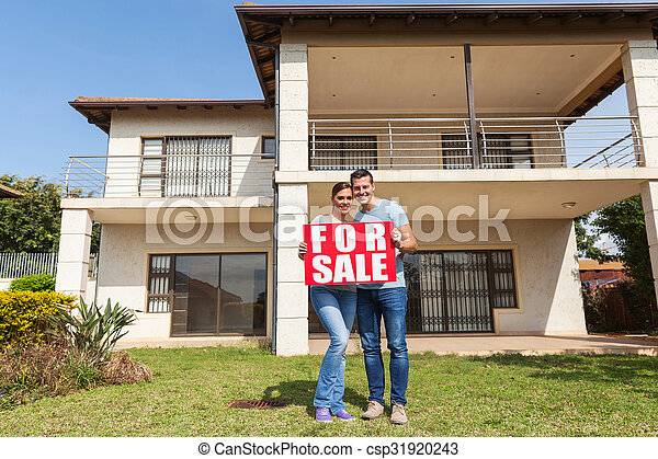 couple holding for sale sign in front of house - csp31920243