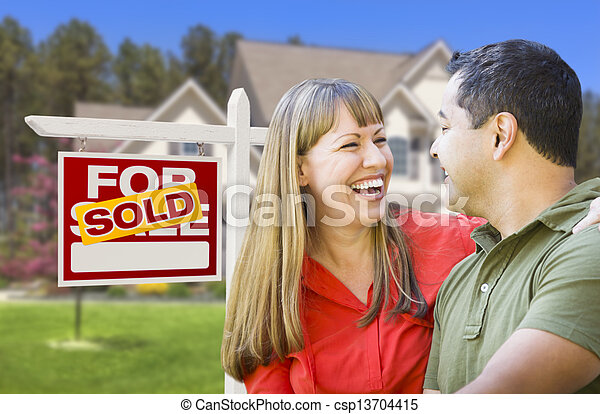 Couple in Front of Sold Real Estate Sign and House - csp13704415