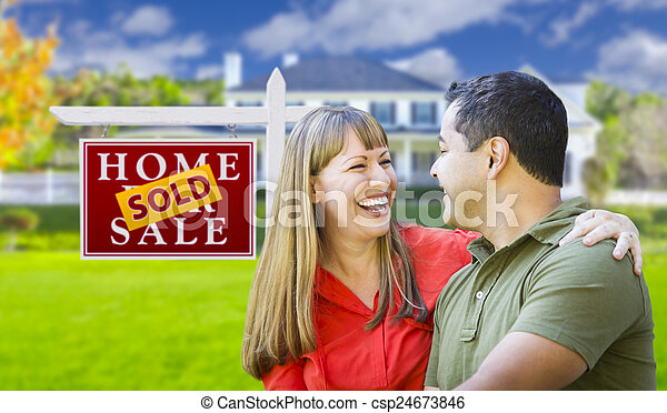 Couple in Front of Sold Real Estate Sign and House - csp24673846