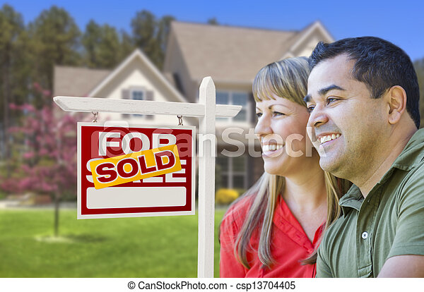 Couple in Front of Sold Real Estate Sign and House - csp13704405