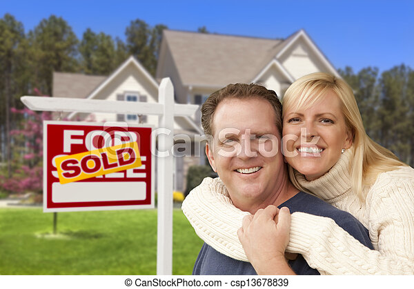 Couple in Front of Sold Real Estate Sign and House - csp13678839