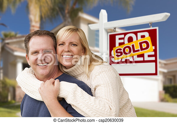 Couple in Front of Sold Real Estate Sign and House - csp20630039