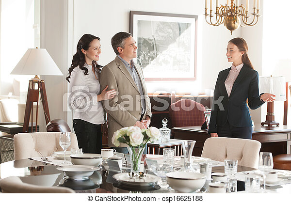 Couple in furniture store. Cheerful middle-aged couple choosing furniture in store while sales clerk consulting them - csp16625188