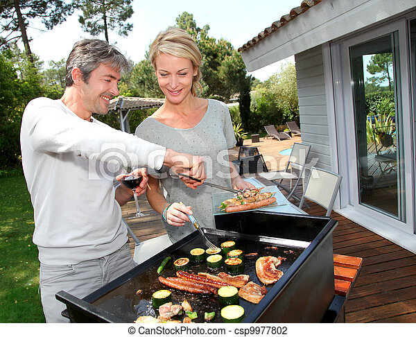 Couple in garden cooking meat on barbecue - csp9977802