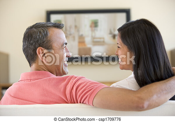 Couple in living room watching television smiling - csp1709776