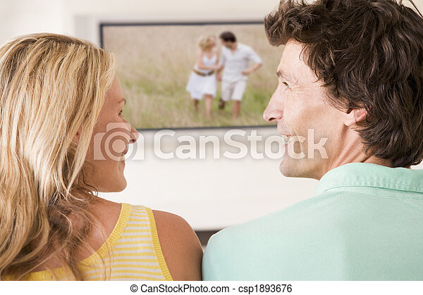 Couple in living room watching television smiling - csp1893676
