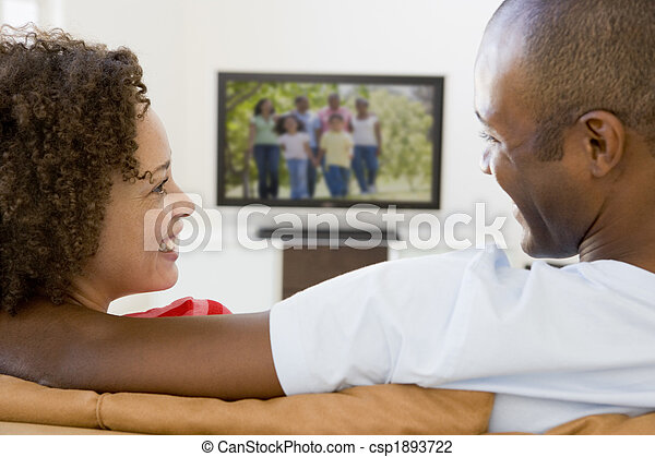 Couple in living room watching television smiling - csp1893722
