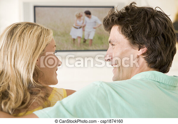 Couple in living room watching television smiling - csp1874160