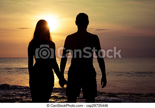 Couple De Dos couple in love back light silhouette on sea at the sunset time.