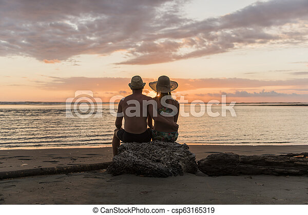 Couple in love having romantic tender moments at sunset on the beach - csp63165319