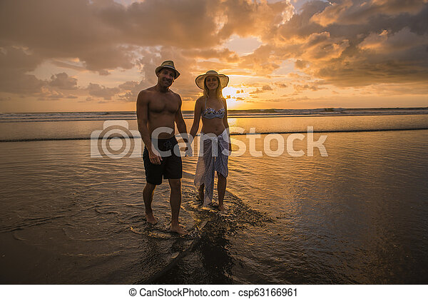 Couple in love having romantic tender moments at sunset on the beach - csp63166961