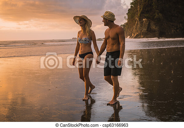 Couple in love having romantic tender moments at sunset on the beach - csp63166963