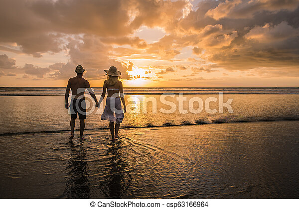 Couple in love having romantic tender moments at sunset on the beach - csp63166964