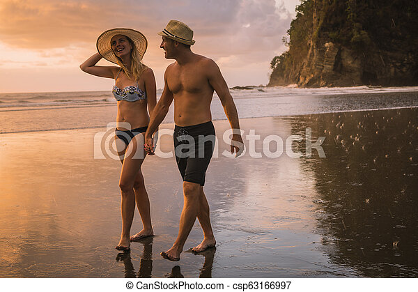 Couple in love having romantic tender moments at sunset on the beach - csp63166997