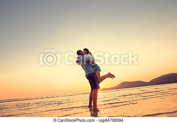 Couple in love having romantic tender moments at sunset on the beach. - csp64708094
