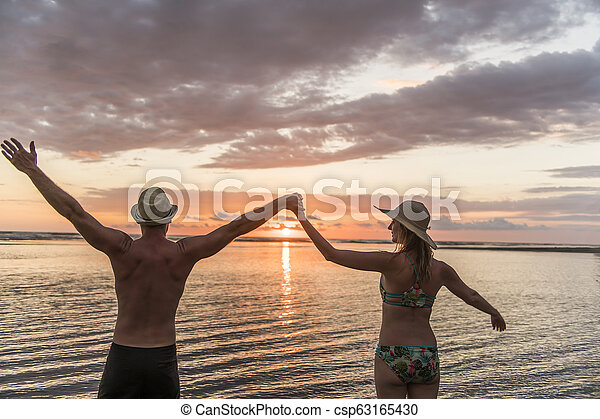 Couple in love having romantic tender moments at sunset on the beach - csp63165430