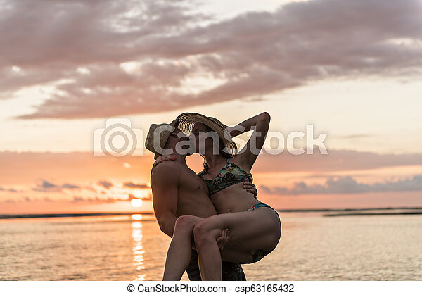 Couple in love having romantic tender moments at sunset on the beach - csp63165432