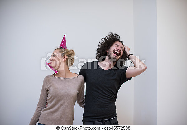couple in party hats blowing in whistle - csp45572588