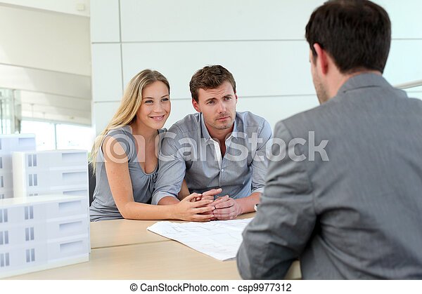 Couple in real-estate agency talking to construction planner - csp9977312