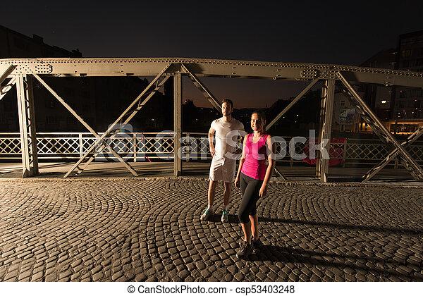 couple jogging across the bridge in the city - csp53403248