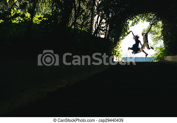 couple jumping in the end of tunnel with trees - csp29440439