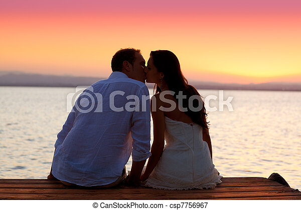 couple kissing at sunset sitting in jetty - csp7756967