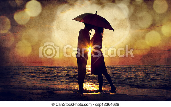 Couple kissing under umbrella at the beach in sunset. Photo in old image style. - csp12364629