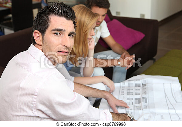 Couple looking at a blueprint with their architect - csp8769998