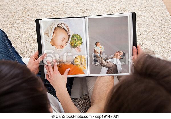 Couple Looking At Photo Album - csp19147081