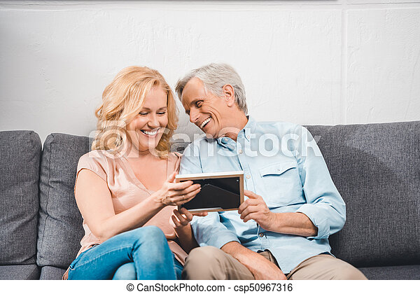 couple looking at photo frame - csp50967316