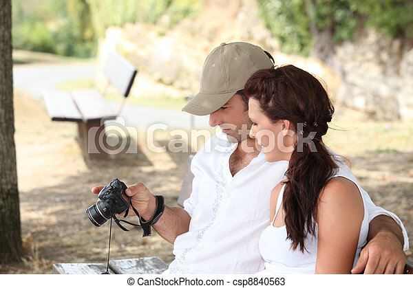 Couple looking at photos on camera - csp8840563