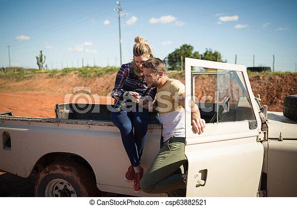 Couple looking at photos on digital camera - csp63882521
