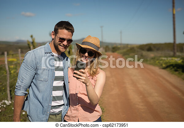 Couple looking at photos on mobile phone - csp62173951