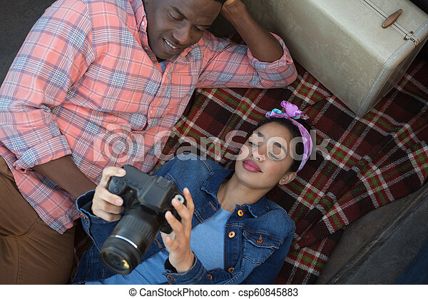 Couple looking at pictures on camera - csp60845883