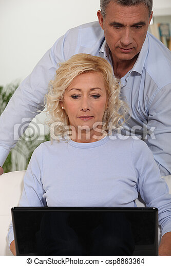 Couple looking at their laptop - csp8863364