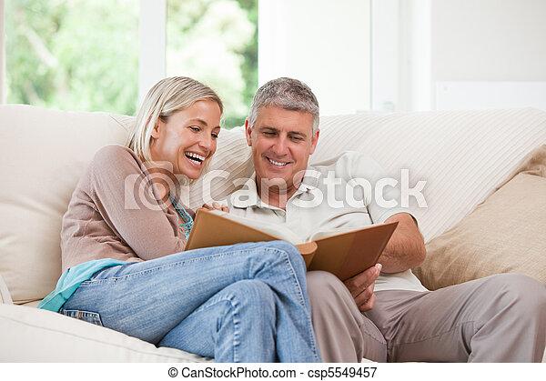 Couple looking at their photo album - csp5549457
