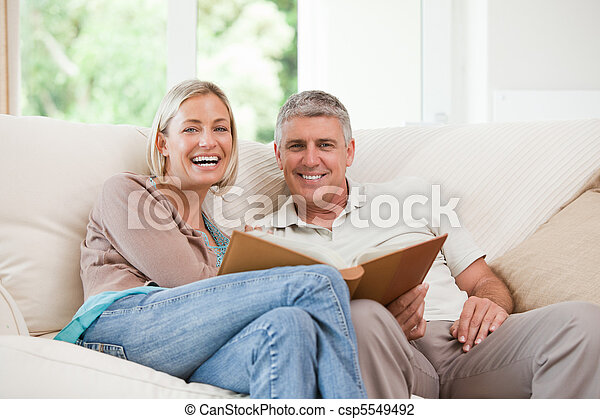 Couple looking at their photo album - csp5549492