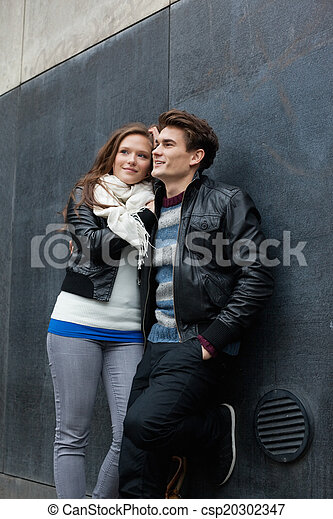 Couple Looking Away While Leaning On Wall - csp20302347