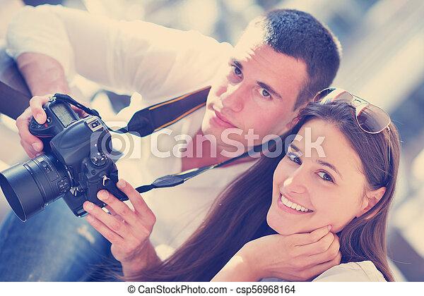 couple looking photos on camera - csp56968164