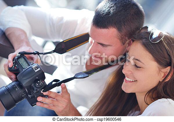 couple looking photos on camera - csp19600546