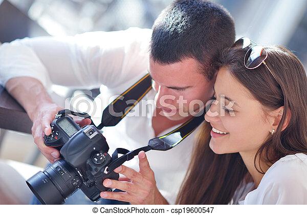 couple looking photos on camera - csp19600547