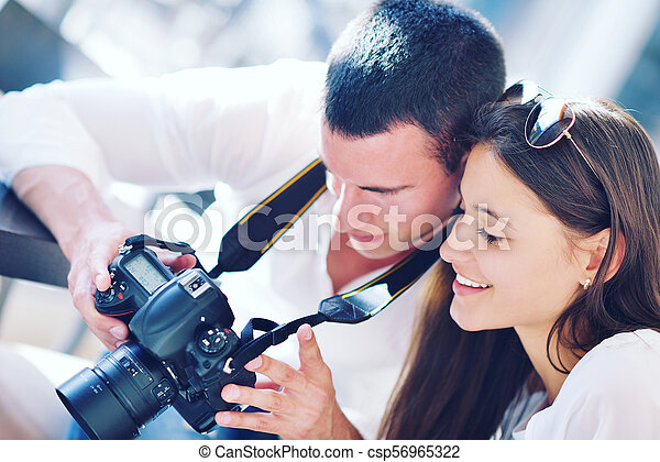 couple looking photos on camera - csp56965322