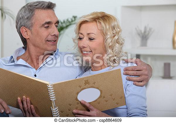 Couple looking through photo album - csp8864609