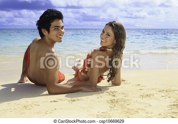 couple lounging on a hawaii beach - csp10669629