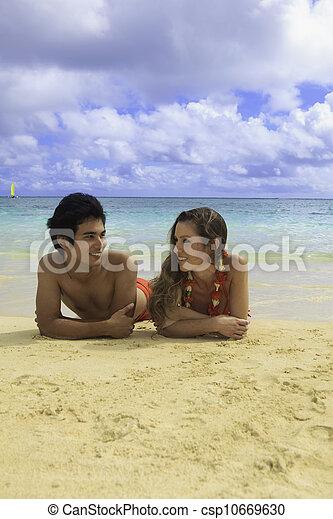 couple lounging on a hawaii beach - csp10669630
